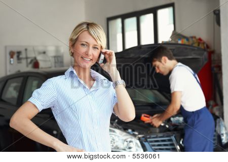 mechanic talking with female client in auto repair shop. poster