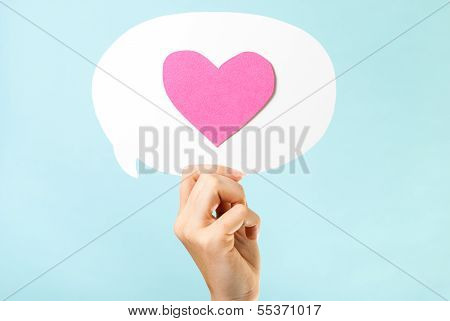 Pink love message concept on blue background. Hand holding a Speech bubble with a pink paper heart