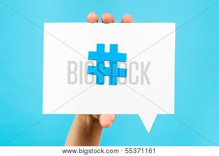 Hand holding a speech bubble with a Hashtag internet notification concept on blue background