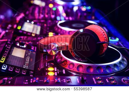 Dj mixer with headphones at a nightclub poster