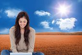 Composite image of beautiful smiling brunette sitting on floor using laptop poster