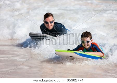 Father and son surfing on boogie boards