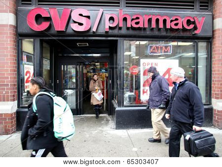 NEW YORK CITY - FEB. 18, 2014: Pedestrians walk past a CVS Pharmacy n New York City on Tuesday,  February 18, 2014. CVS is the retail division of CVS Caremark.