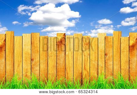 wooden fence with green grass and field on background