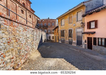 Narrow cobblestone street between brick wall and typical italian house in town of La Morra in Piedmont, Northern Italy.