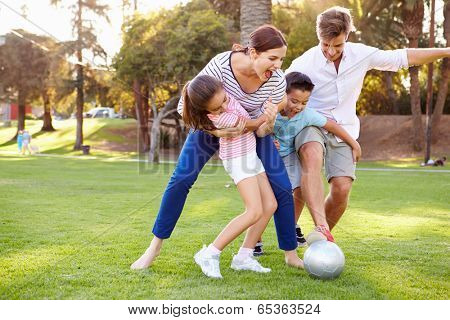 Family Playing Soccer In Park Together
