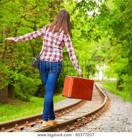 girl with retro brown suitcase walking on the railway poster