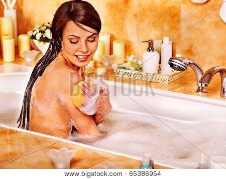 Young woman take bubble bath in bathroom.