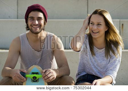 Portrait of a young, lovely, happy skateboarding couple on concrete steps on a bright, summer afternoon, with a pleasant, friendly atmosphere.