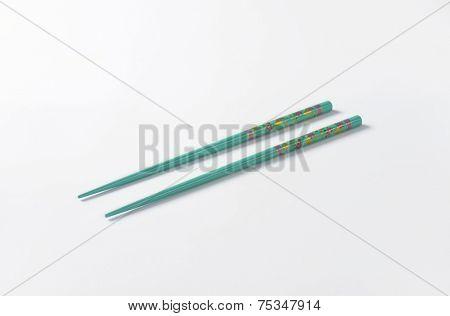 pair of blue chopsticks on white background