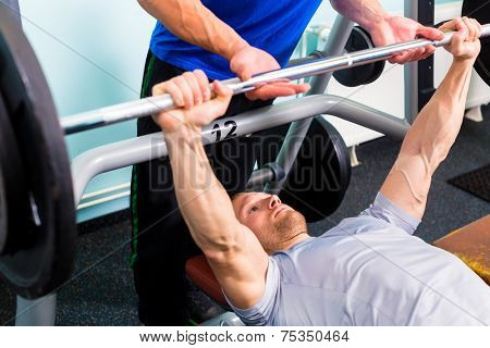 Men in sport gym training with barbell for fitness