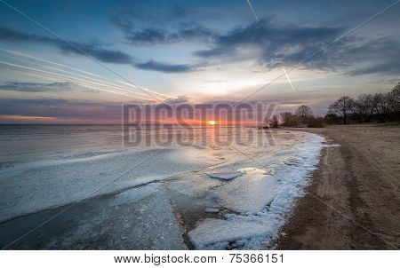 Sunset at frozen bay. Ice on the water and sand beach line poster