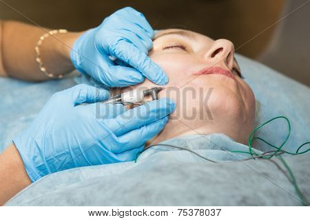 MOSCOW - OCTOBER 24: Cosmetologist performs an injections at the international exhibition of professional cosmetics and beauty salon equipment INTERCHARM on October 24, 2014 in Moscow