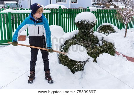 a teenager shoveling the new snow from a path. onset of winter