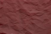 the abstract textured background from crumpled mesh with small cells synthetic fabric of crimson color poster