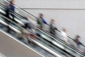 People travelling on escalator taking with slow shutter speed to show movement poster