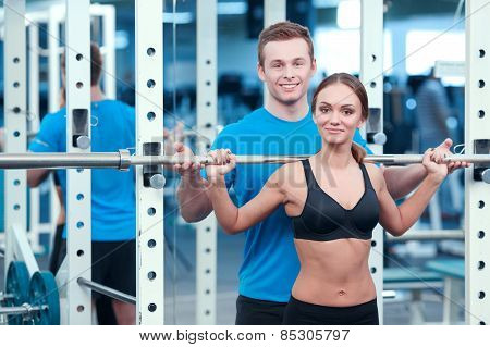 Working out legs exercises. Concentrated young beautiful woman in sports clothing doing exercises in the gym with a barbell while her sports instructor controlling the workout poster