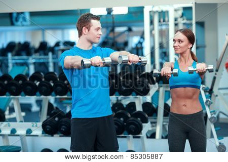 Weight exercise. Beautiful young woman in sports clothing exercising with dumbbells while standing in health club with her sports instructor poster