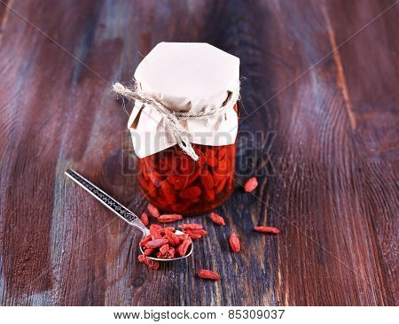 Goji berries in glass bottle wrapped with paper and silver spoon on rustic wooden table background