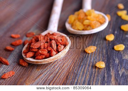 Raisins and Goji in spoons on rustic wooden table background