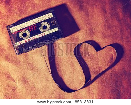 an old dirty grungy scratched up audio cassette tape in the shape of heart (focus on the words) on a brown paper texture background good for valentine's day or love greeting cards (SHALLOW DOF)