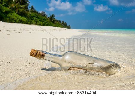 Message In A Bottle Washed Ashore On A Tropical Beach.