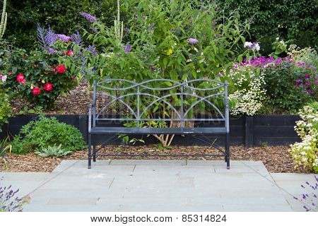 Metal bench on patio in in garden with flowers