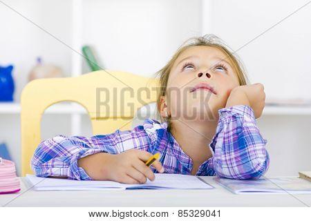 Kid thinking wile doing her homework