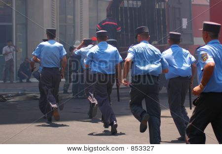 Policemen With Batons Running Away