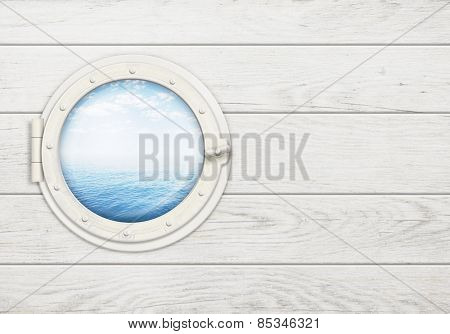 ship window or porthole on white wooden wall with sea or ocean horizon