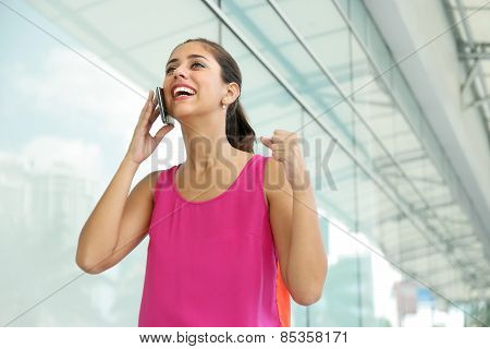 Portrait of young woman talking on mobile phone getting good news and exulting for joy poster