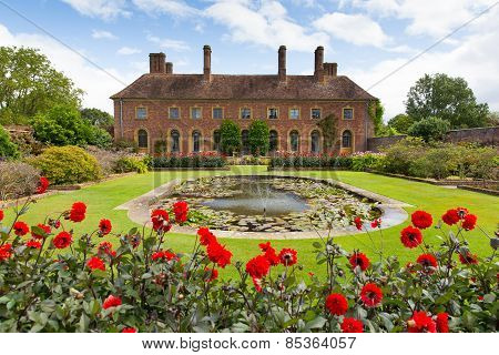Strode House Barrington Court near Ilminster Somerset England uk Lily pond garden and red dahlias