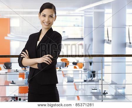 Attractive, happy, asian businesswoman at high-tech business office with arms crossed. Smiling, arms crossed, standing upstairs. Copyspace.