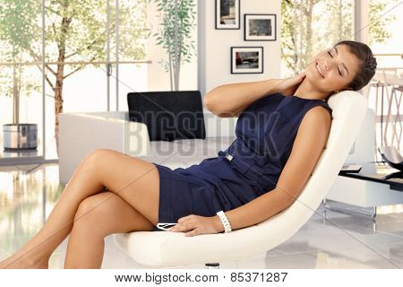 Attractive young brunette caucasian woman in blue dress resting in leather chair at trendy home. Smiling, caressing herself, eyes closed, relaxing.