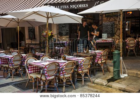 NICE, FRANCE - OCTOBER 2, 2014: Outdoor patio of restaurant L'Escalinada is ready for customers on Rue Pairoliere, a quaint pedestrian street in old Nice.