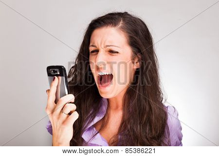 Angry woman shouting to a cell phone