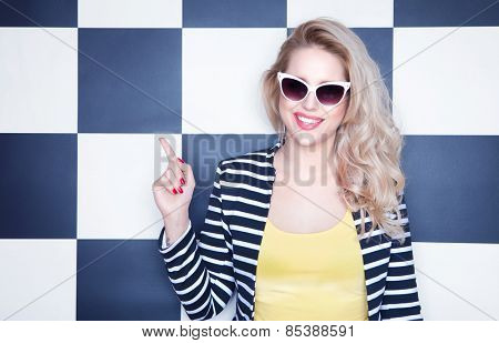 Attractive young woman wearing sunglasses on checkered background, pointing up, beauty and fashion concept