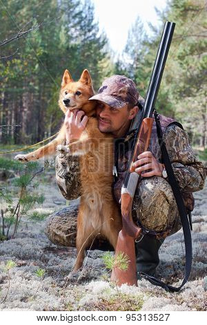 The hunter with gun embraces his dog poster