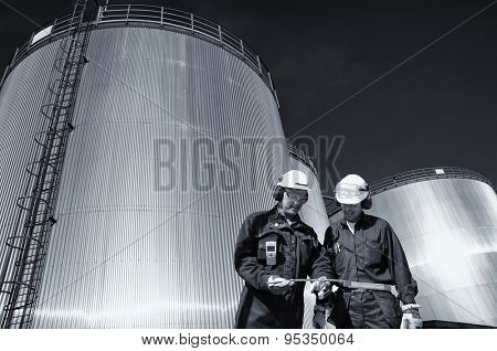 two oil workers with large fuel-tanks in background, slight blue toning concept