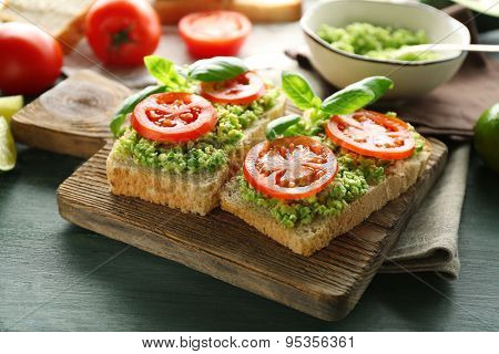 Vegan sandwich with avocado and vegetables on cutting board, on wooden background