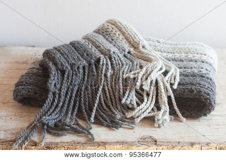 wool grey scarf with tassels closeup on wooden background