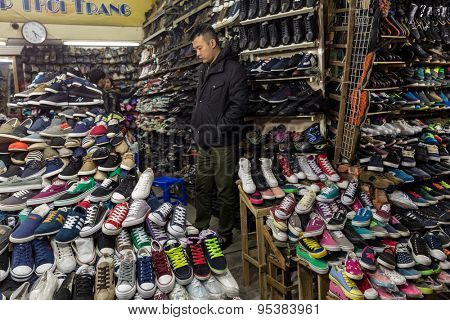HANOI, VIETNAM, DECEMBER 15, 2014 : An undecided man is taking a look in a shop specialized in the selling of shoes in Hanoi, Vietnam