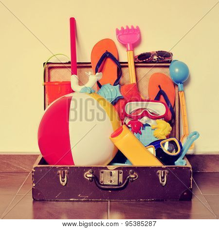 an old cardboard suitcase full of beach items, such as diving masks, pails and shovels, a beach ball, sunblock or flip-flops, placed on the floor, with a retro effect