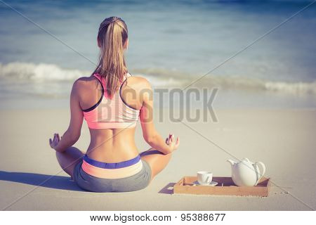 Back turned fit woman doing yoga on the beach