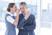 Secretive business colleagues whispering in the office poster
