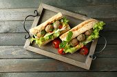 Homemade Spicy Meatball Sub Sandwich on tray, on wooden table background poster
