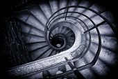 Black and White High Angle View of Spiral Staircase Winding Downward in Historical Building, Looking Down at Bottom of Stairs in Elegant Old Building poster