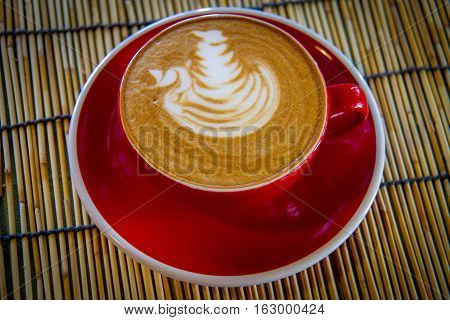 Cappuchino or latte coffee in a red cup on wooden board