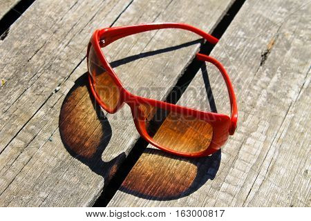 Red sunglasses on the old  wooden background
