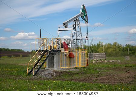 oil pump jack with a green field in background